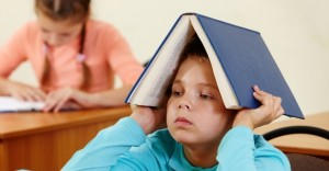 Cute schoolboy keeping open book on head in classroom